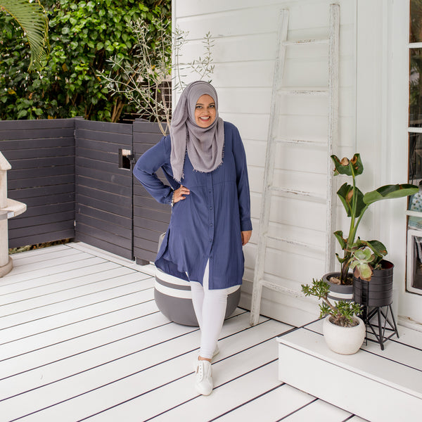 Faaiza wearing our Danielle technical shirt dress in  steel blue with a grey Hijab,  white leggings and white sneakers.