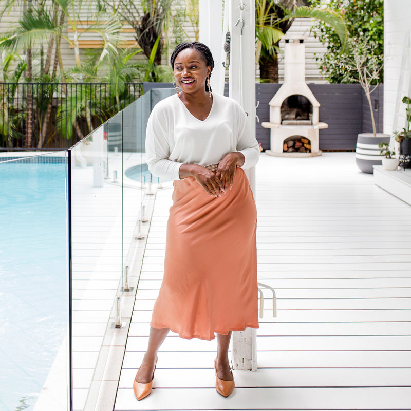 Sonia is wearing Deborah Midi skirt in Toffee with Jenny swing knit in Ivory and tan shoes