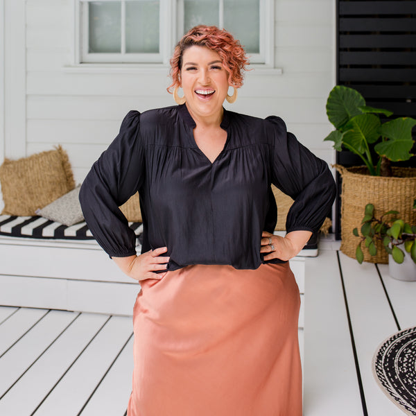Jo is wearing Felicity blouse in black tucked into Deborah Midi skirt in Toffee