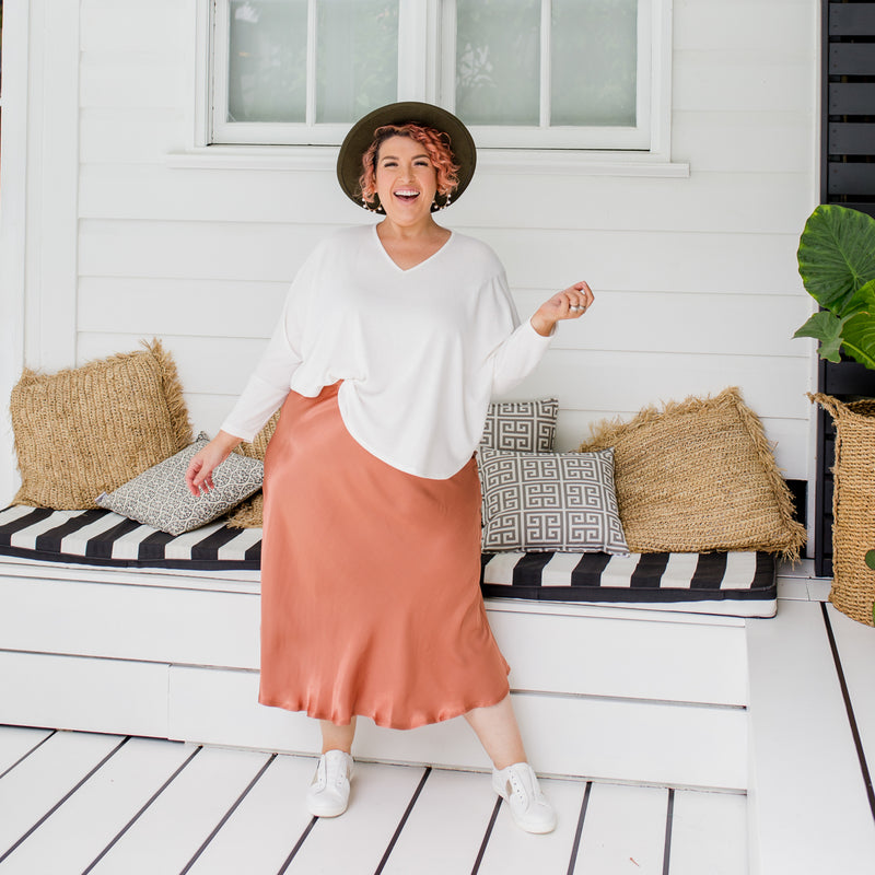 Jo  is wearing Deborah Midi skirt in Toffee with Jenny swing knit in Ivory and white sneakers