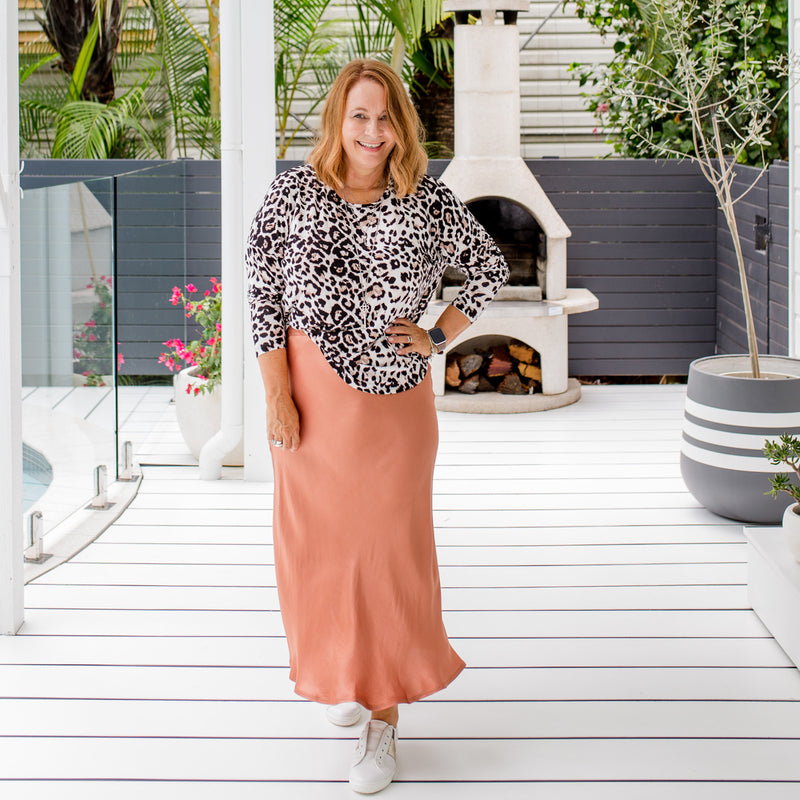 Karen is wearing  Deborah Midi skirt in Toffee with Ingrid Long sleeve tee in animal print and white sneakers