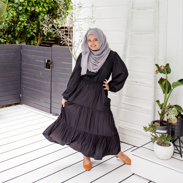 Faaiza is wearing Edwina billow sleeve mid dress in black with a grey Hijab and tan shoes