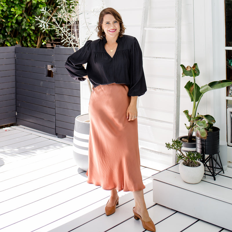 Bec is wearing Deborah Midi skirt in Toffee with Felicity blouse in black and tan shoes