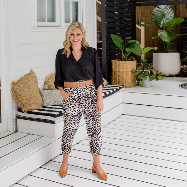 Brooke is wearing Felicity Billow sleeve blouse in black tucked into Leanne Joggy pants in animal print with tan belt and shoes