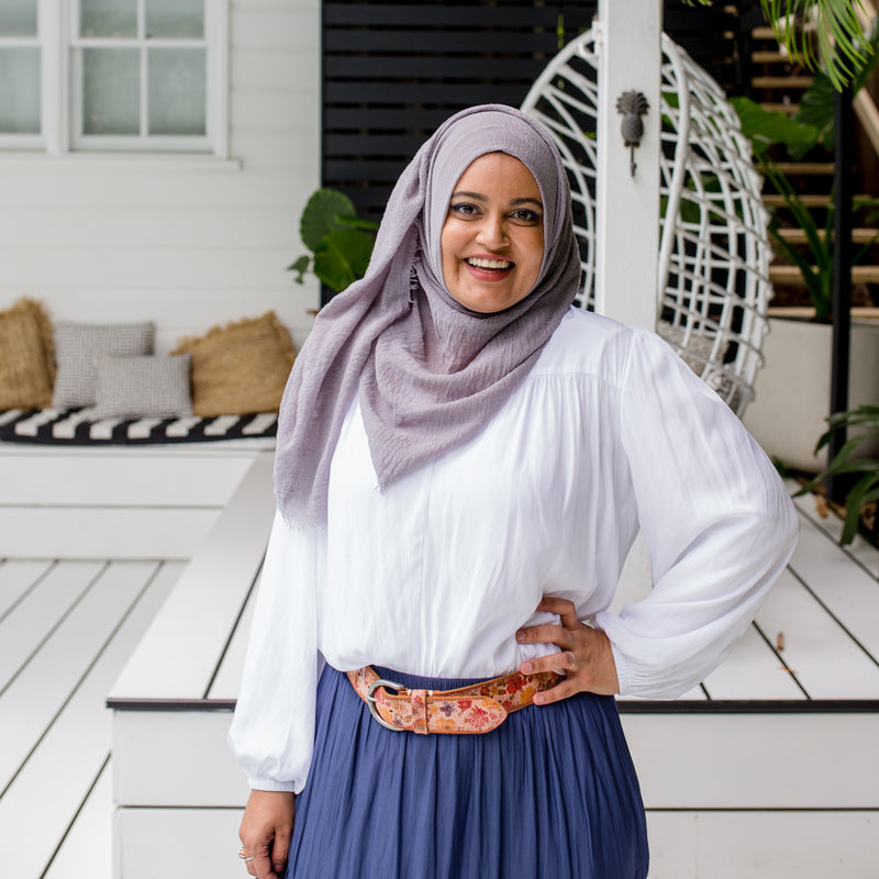Faaiza is wearing our Felicity technical billow blouse in white tucked into Sophie maxi skirt in steel blue with floral belt and grey Hijab.
