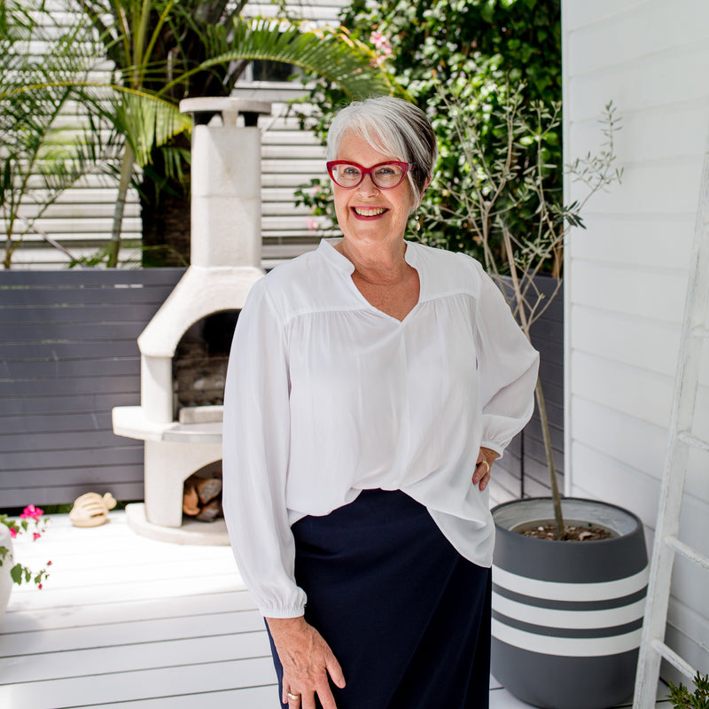 Jan wearing our Felicity technical billow blouse in white tucked into Fiona  scuba pencil skirt in navy. She's also wearing red glasses.