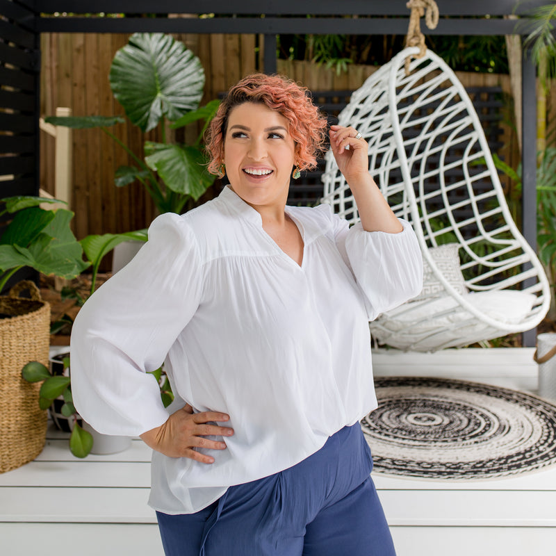 Jo is wearing Felicity technical billow blouse in white tucked into Maddy technical crop pant in steel blue.