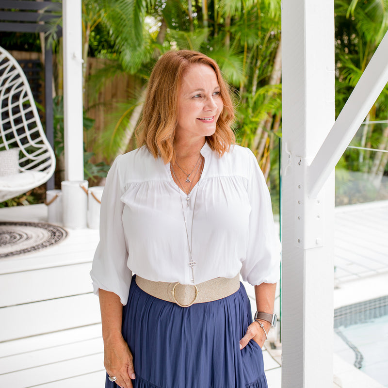 Karen is wearing our Felicity technical billow blouse in white tucked into Sophie maxi skirt in steel blue with natural colour belt.