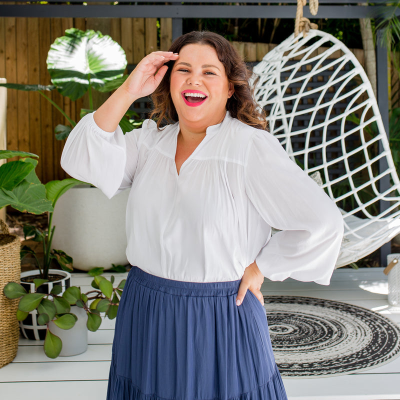Stacey is wearing Felicity technical billow blouse in white tucked into  Sophie technical tiered maxi skirt in steel blue.