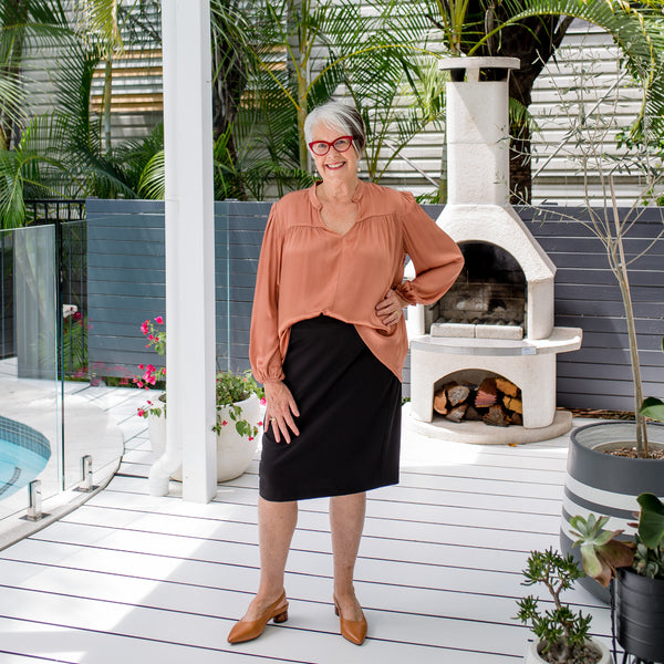 Jan wearing our Gwendolyn Satin billow sleeve blouse in toffee tucked into Fiona scuba pencil skirt in black with tan shoes. She's also wearing red glasses.