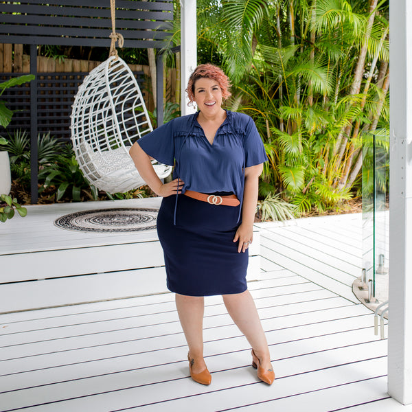 Jo is wearing our Kim technical blouse in steel blue tucked into Fiona scuba pencil skirt in navy with tan belt and shoes.