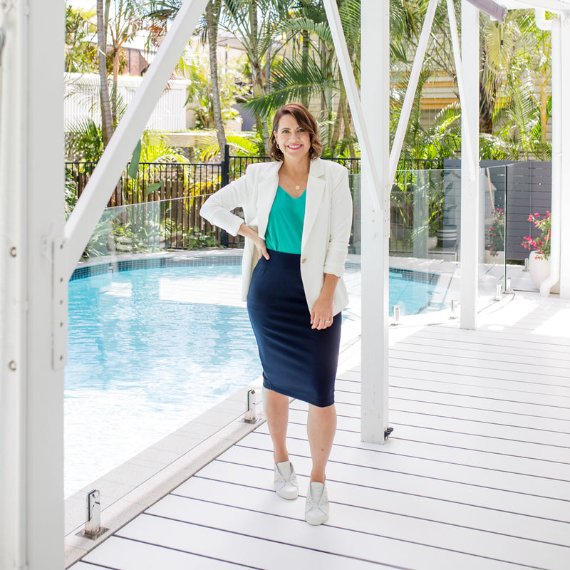 Bec is wearing our Helen scuba blazer in Ivory on top of Rachael technical cami in green tucked into Fiona scuba pencil skirt in navy and white sneakers.