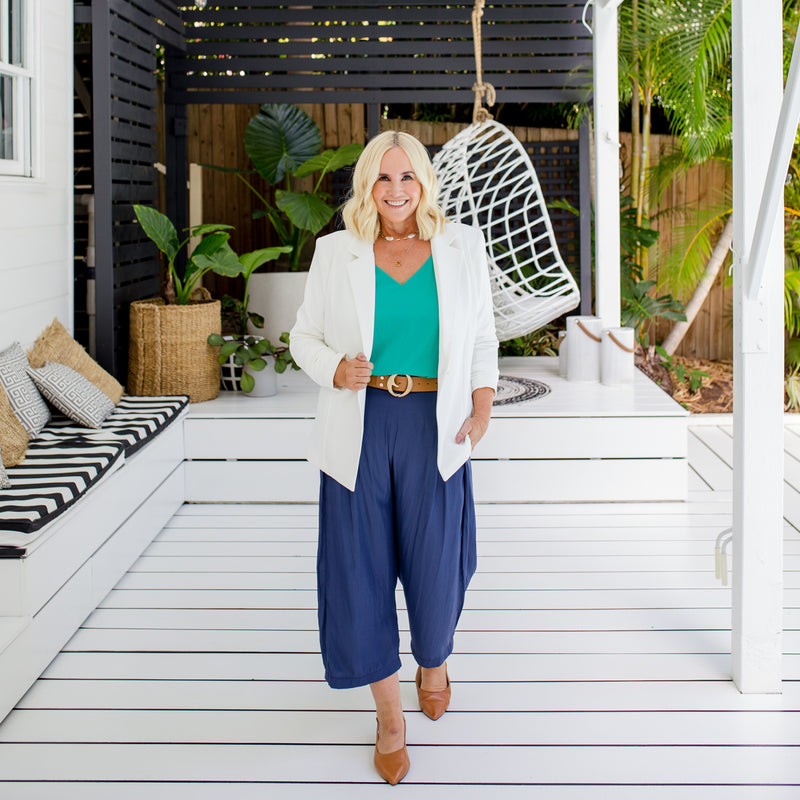 Nikki is wearing our Helen scuba blazer in Ivory on top of Rachael technical cami in green tucked into Maddy technical crop pant in steel blue with tan coloured belt and tan shoes.
