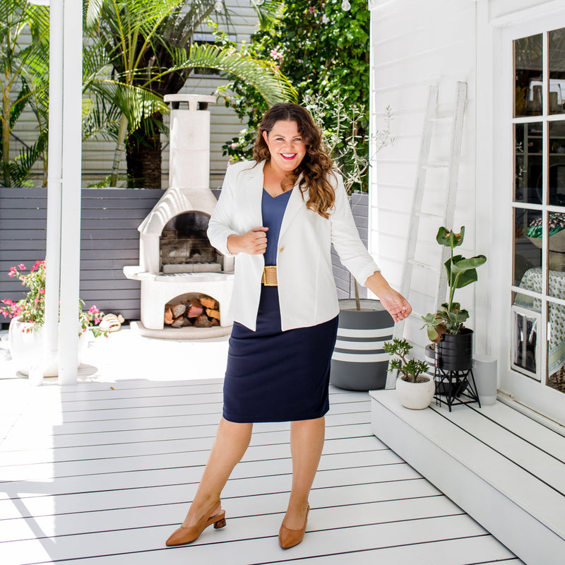 Stacey is wearing our Helen scuba blazer in ivory on top of Rachael technical cami in steel blue tucked into Fiona scuba pencil skirt in navy with tan belt and shoes.