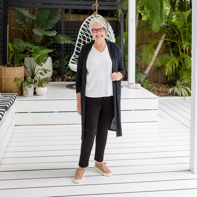 Jan wearing our black jalena longline cardigan over our Sharon long sleeve tee in white with our Suzie jogger pants in black.