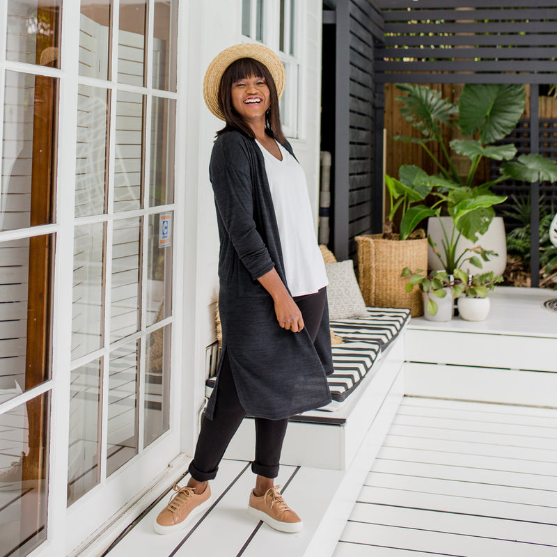 Sonia wearing our Jalena longline cardigan in black over our Sharon long sleeve top in white and Suzie Ponte jogger pants in black. She has styled this with brown sneakers and a straw hat.