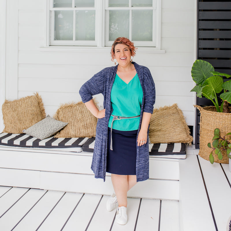 Jo is wearing our Jalena longline cardigan in navy marle on tope of Rachael technical cami in green and Fiona scuba pencil skirt in navy with striped belt and white sneakers.