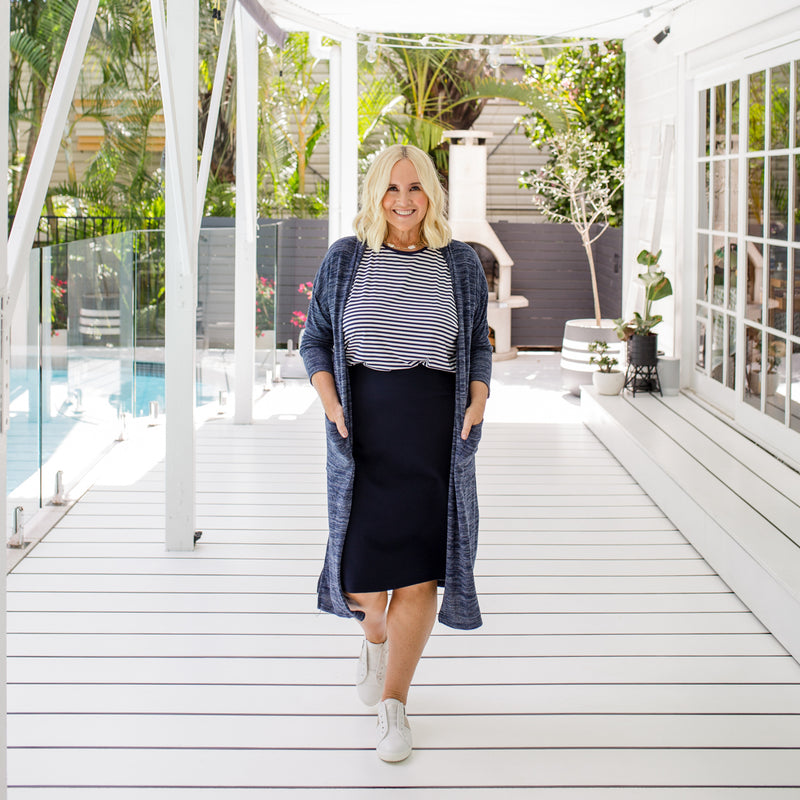 Nikki  is wearing our Jalena longline cardigan in navy marle on top of the Melinda stripe tee in navy and white tucked into  Fiona scuba pencil skirt in navy with white sneakers.