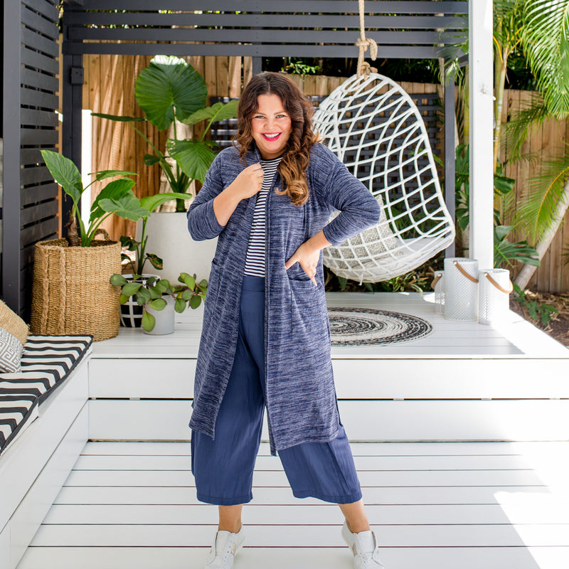 Stacey is wearing our Jalena longline cardigan in navy marle on top of the Melinda stripe tee in navy and white tucked into Maddy technical crop pants in steel blue with white sneakers.