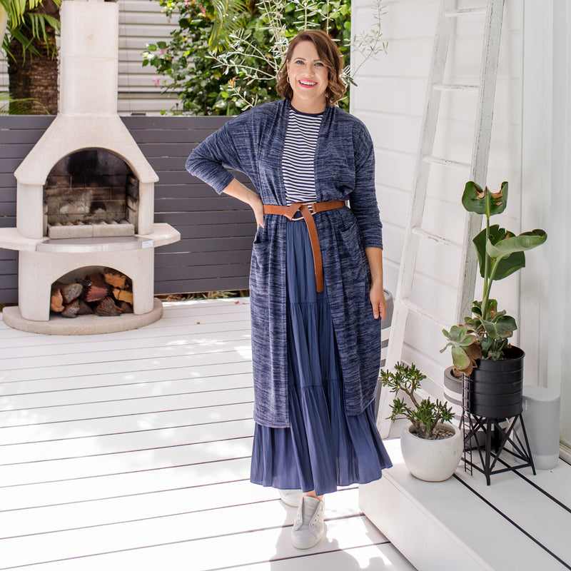 Bec  is wearing our Jalena longline cardigan in navy marle with Melinda stripe tee in navy and white tucked into Sophie technical maxi skirt in steel blue.She's wearing tan belt over the cardigan and white sneakers.