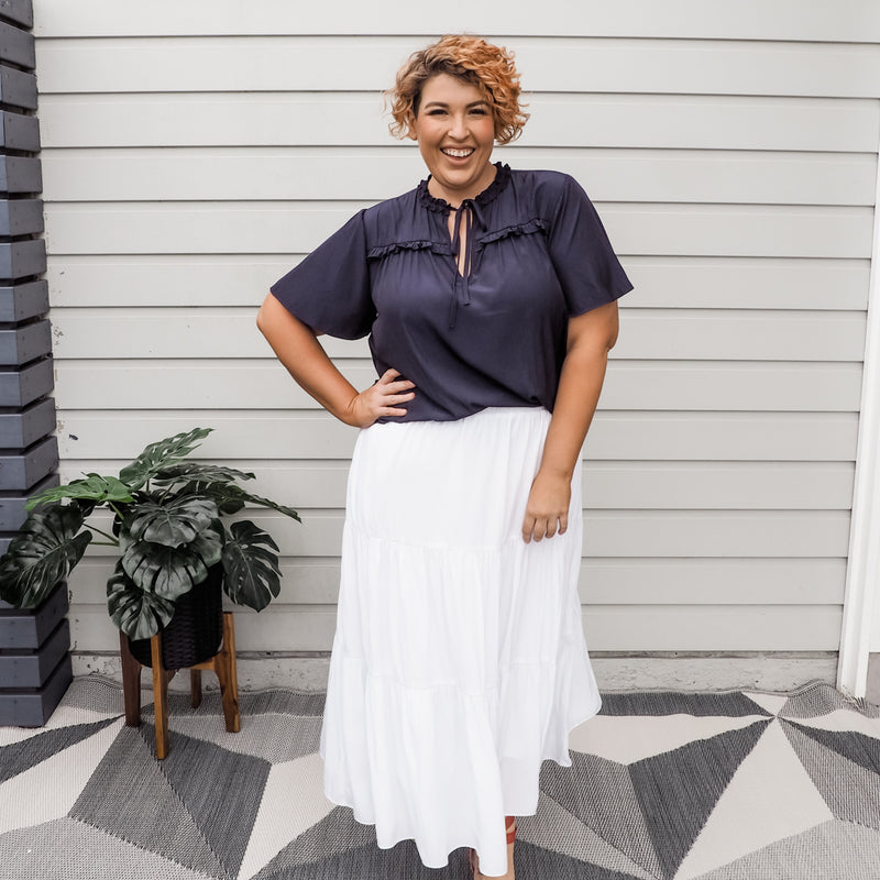 Jo wearing our Kim technical blouse in navy over our white Sophie skirt.