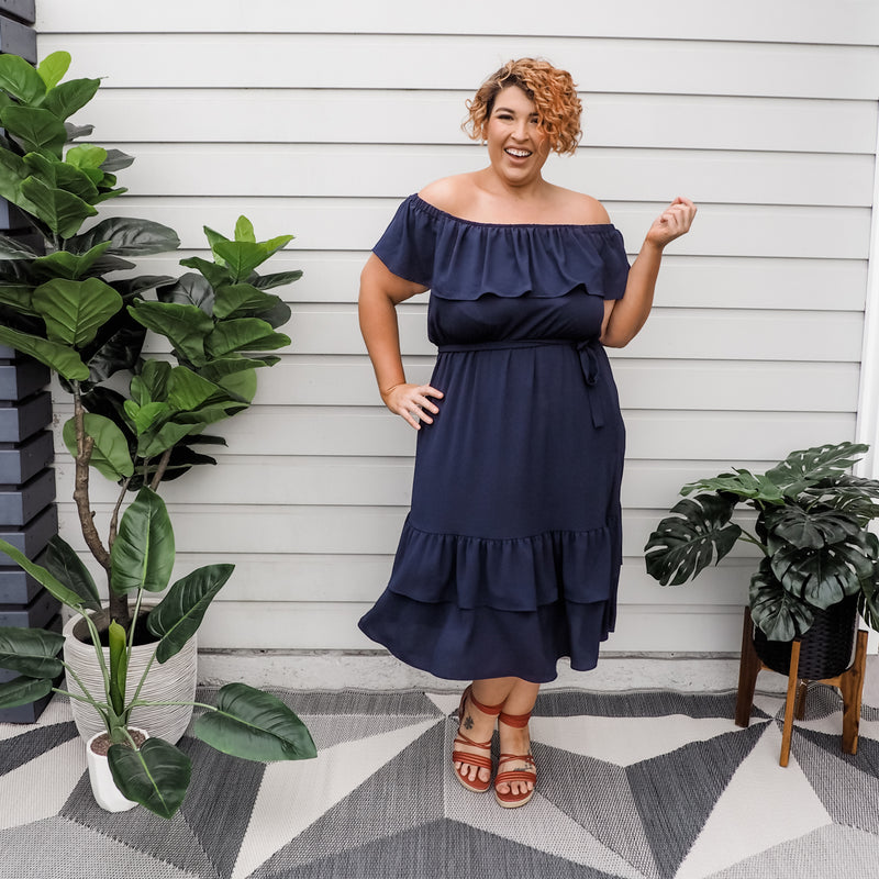 Jo wearing our natalie off-the-shoulder dress in navy with red heels.