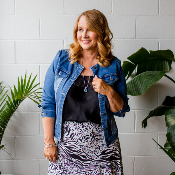 Karen wearing our Jodie denim jacket over our black Lesley Cami which is tucked into our Rylee midi safari skirt.