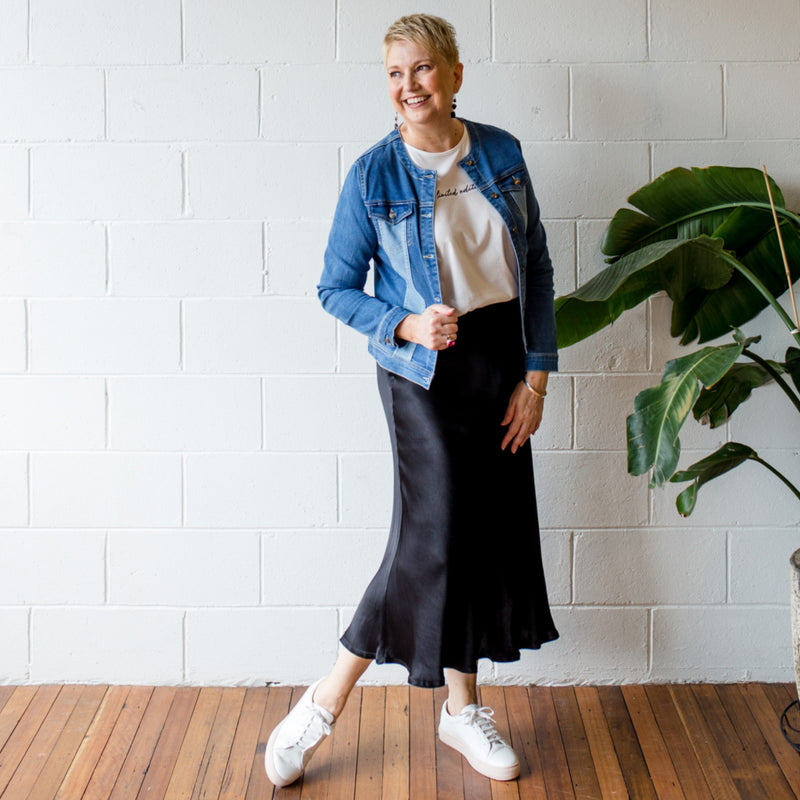 Susan wearing our Jodie denim jacket over our Shanna relaxed tee tucked into our Deborah satin skirt.