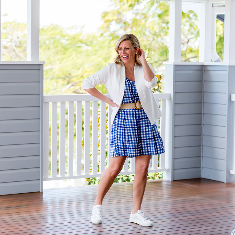 Brooke wearing our Alexa cami in gingham and our grace shorts also in gingham and our Karen Scuba Jacket ivory, paired with a belt and white sneakers