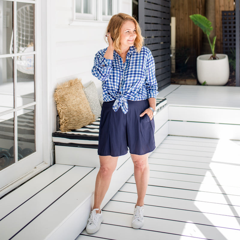 Karen wearing our Kimba shirt gingham and our bec technical shorts in navy paired with white sneakers