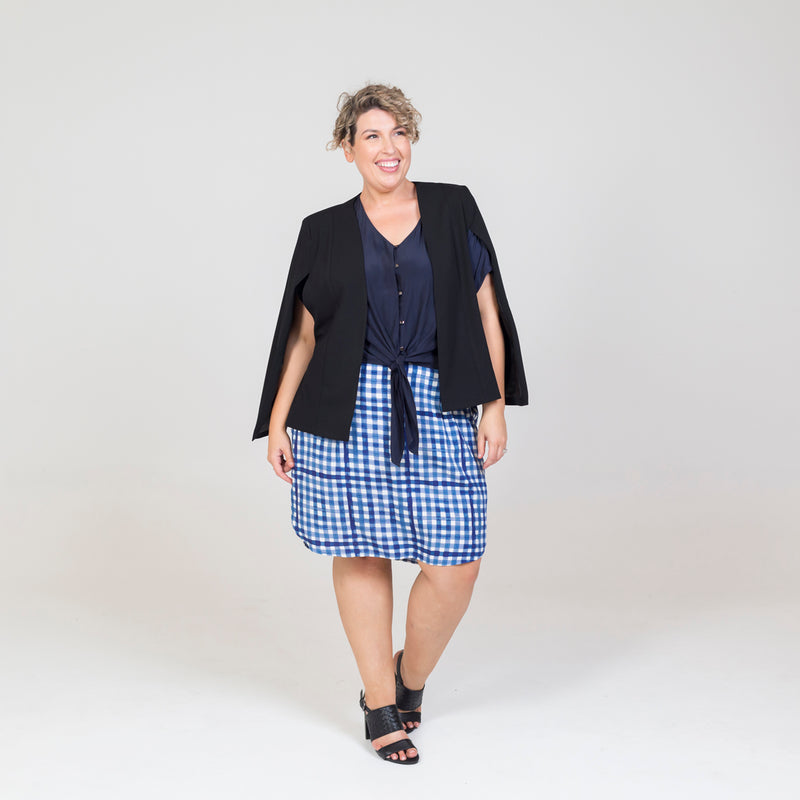 Kirsten cape - black paired with our Cate technical shirt - navy, a gingham print skirt and black sandals