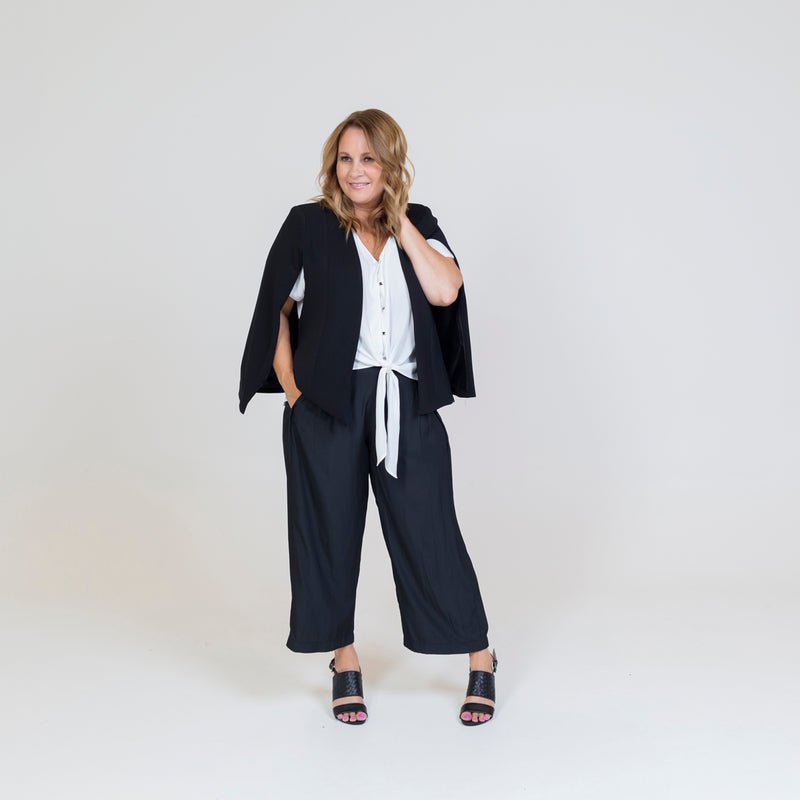 Kirsten cape - black paired with our kate technical shirt in white, our Maddy technical pants and black sandals