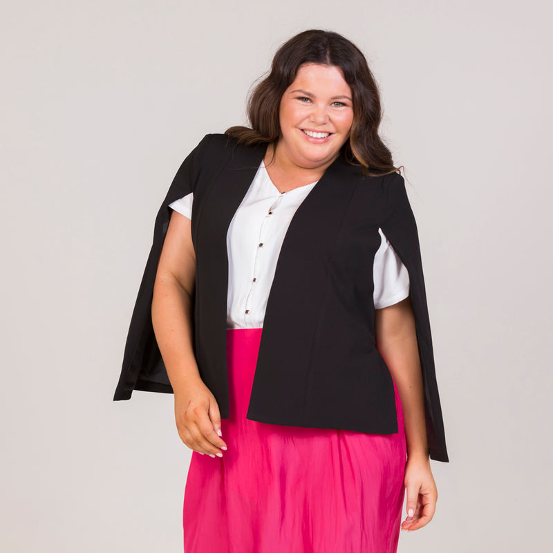 Kirsten cape - black, paired with a white blouse, a pink midi skirt and nude heels