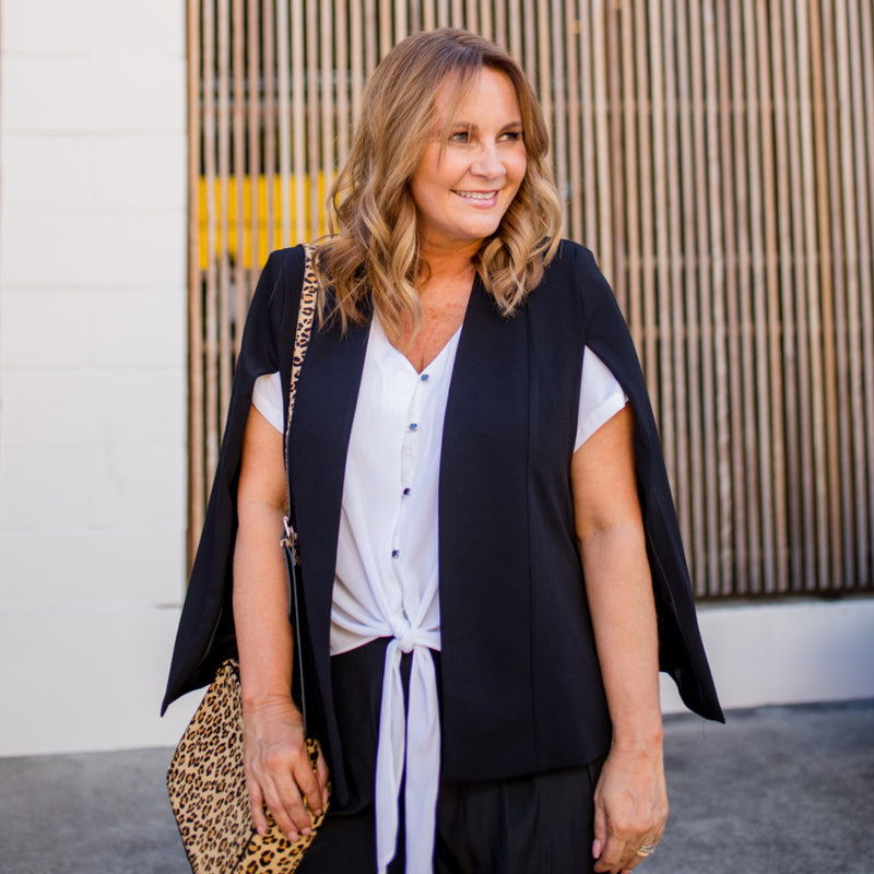 Kirsten cape - black paired with our kate technical shirt in white, our Maddy technical pants in black and a leopard handbag