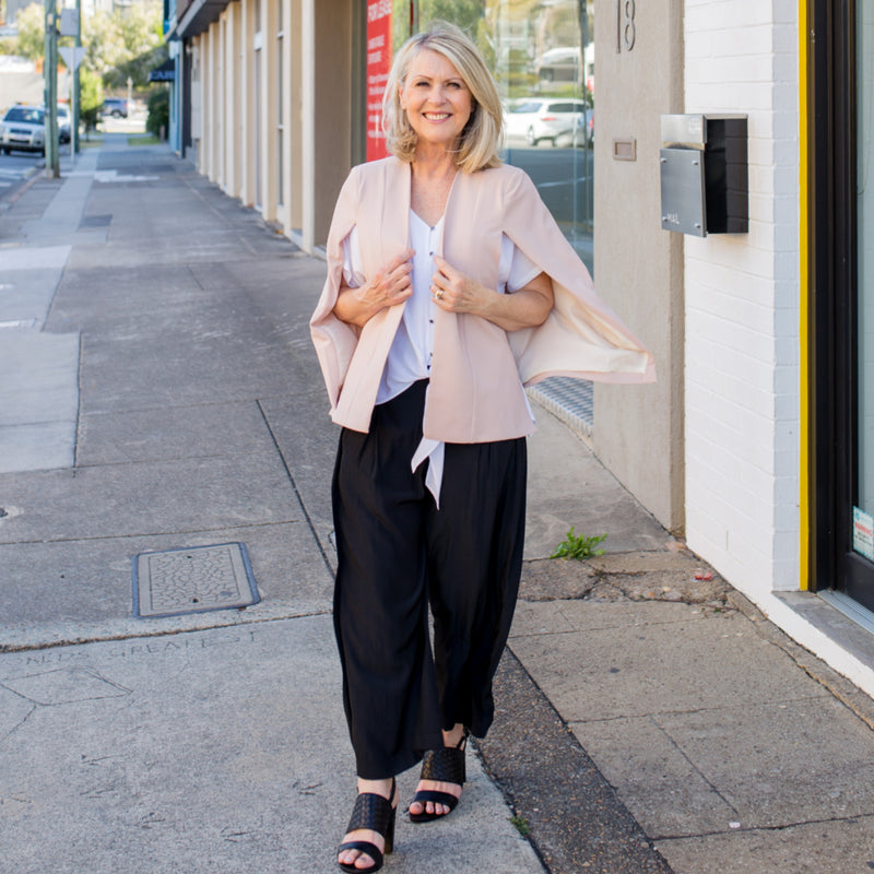Kirsten cape - blush paired with a white blouse, our Maddy technical pants in black and black sandals