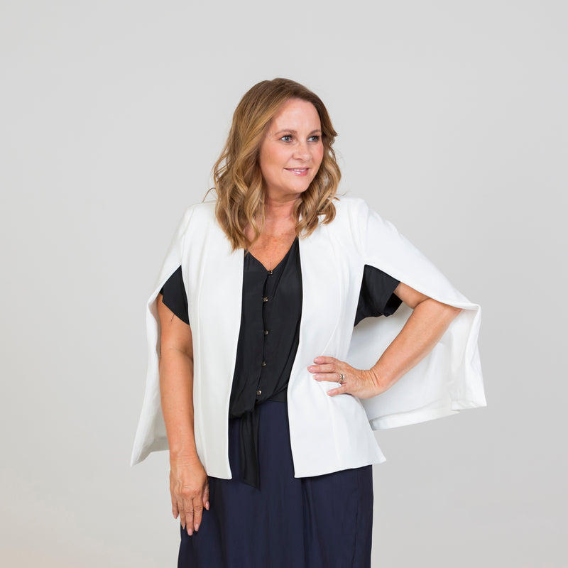Kirsten cape - ivory paired with a black blouse and a navy skirt