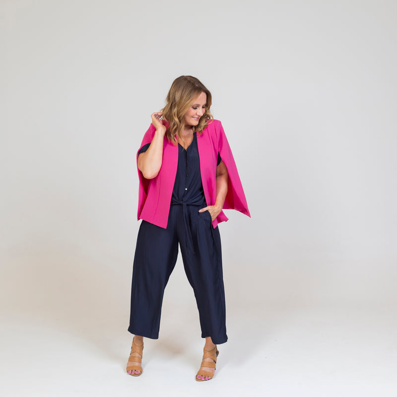 Kirsten cape - paris pink paired with a navy blouse, our Maddy technical pant in navy, and brown heels