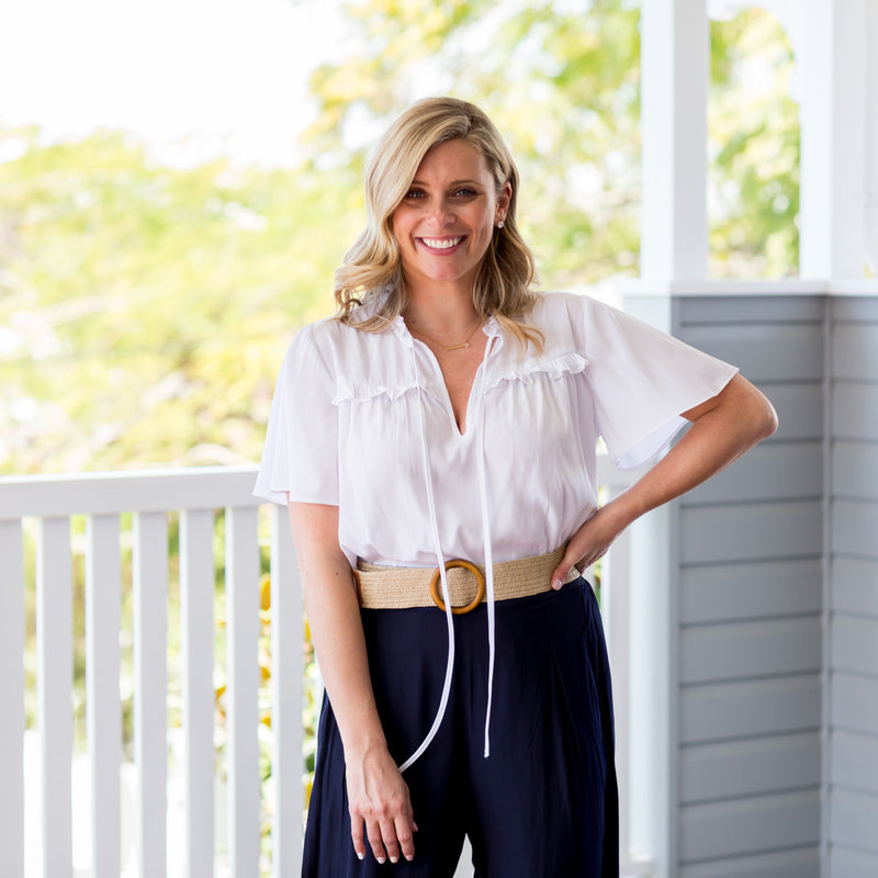 Brooke in our Kim technical blouse white and our Maddy technical crop pant navy, paired with a belt