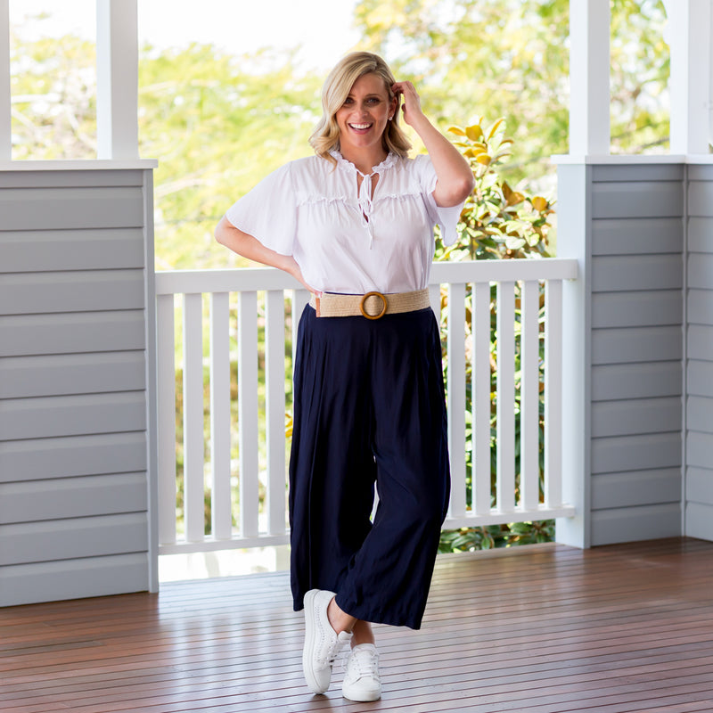 Brooke in our Kim technical blouse white and our Maddy technical crop pant navy, paired with a belt and white sneakers