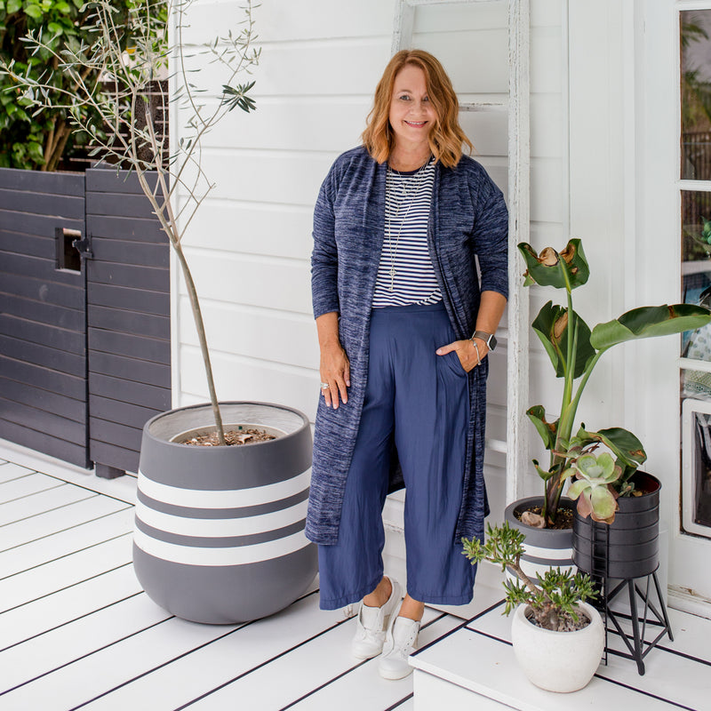 Karen is wearing our Jalena longline cardigan in navy marle on top of  the Melinda stripe tee in navy and white tucked into Maddy technical crop pants in steel blue with white sneakers.