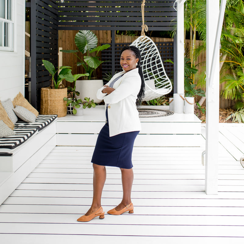 Sonia is wearing our  Helen Scuba blazer in Ivory on top of a Melinda stripe tee in navy and white tucked into Fiona scuba pencil skirt in navy and tan shoes