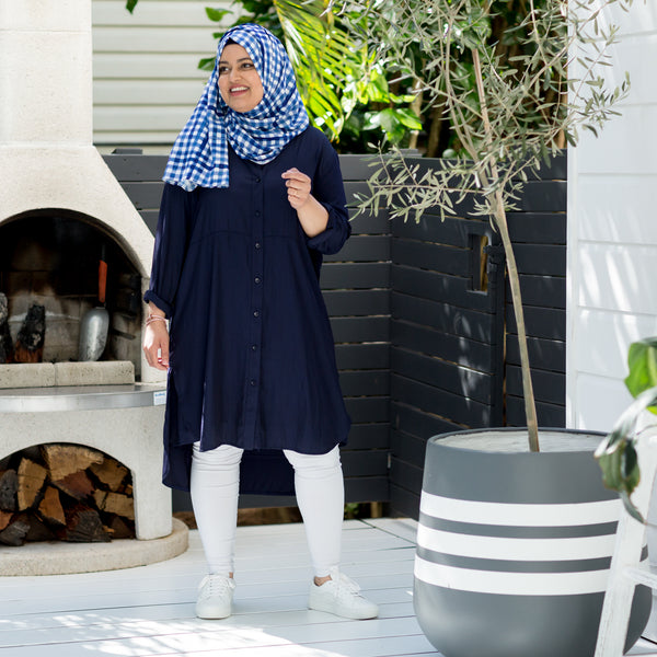 Faaiza wearing our Danielle technical shirt dress navy with our Emily scarf/wrap in gingham, white sneakers and white jeans