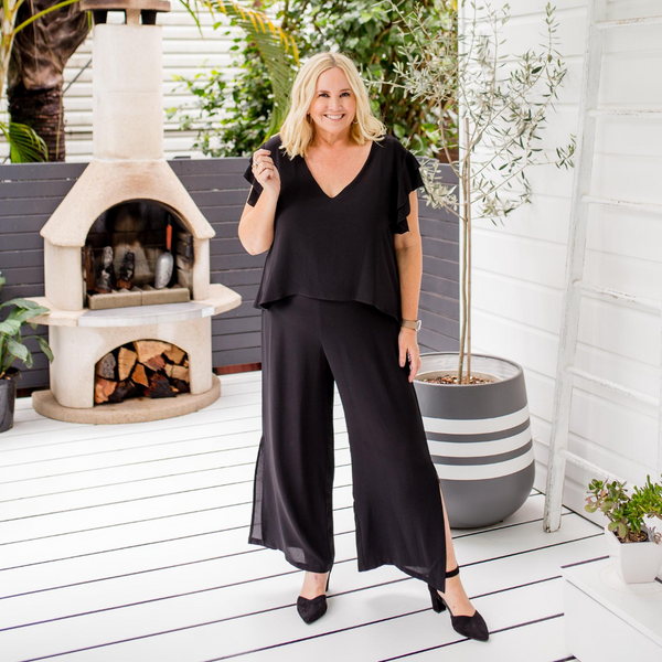Nikki in our Barbara jumpsuit - black with black heels