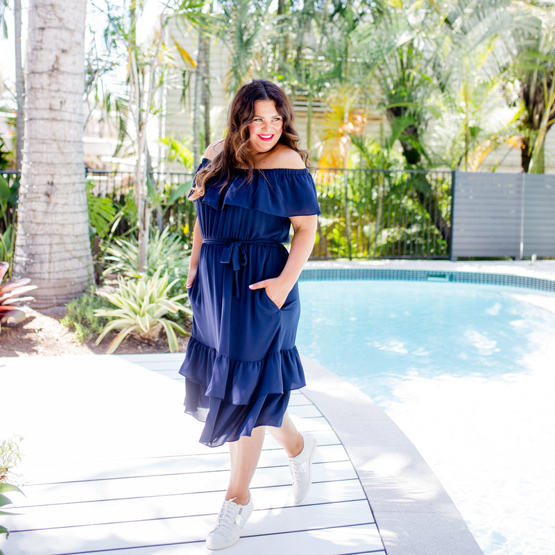 Stacey wearing our natalie off-the-shoulder dress in navy with white sneakers