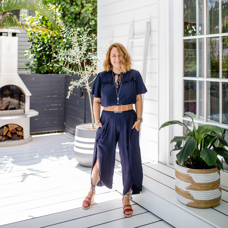 Karen wearing Maria technical split pants in navy with our Kim technical blouse in navy and red heels.