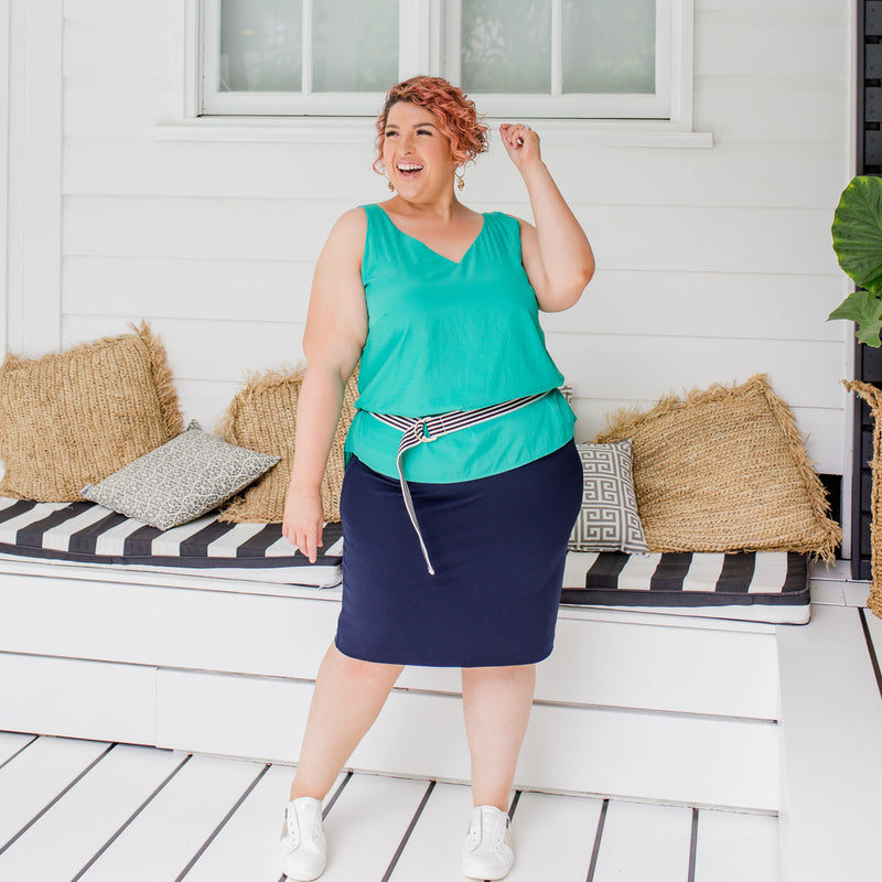 Jo is wearing Rachael technical cami in green on top of Fiona scuba pencil skirt in navy with striped navy and cream belt and white sneakers