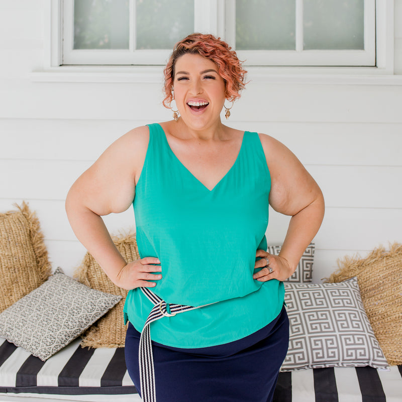 Jo is wearing Rachael technical cami in green on top of Fiona scuba pencil skirt in navy with striped navy and cream belt