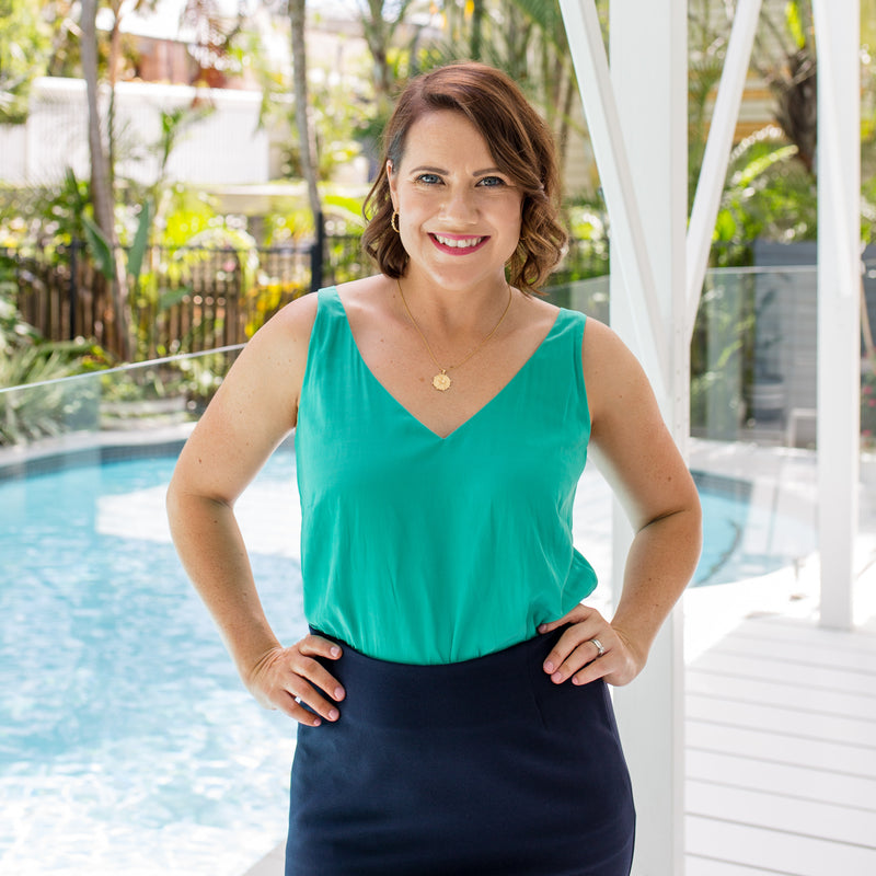Bec is wearing our Rachael technical cami in green tucked into Fiona scuba pencil skirt in navy