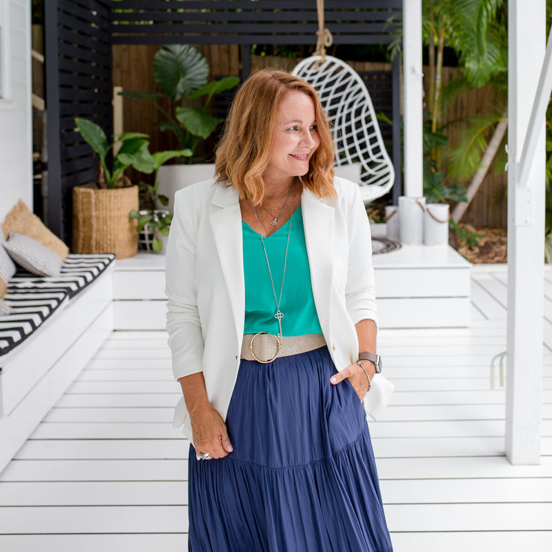 Karen is wearing our Helen scuba blazer in Ivory on top of Rachael technical cami in green tucked into Sophie maxi skirt in steel blue with natural colour belt.