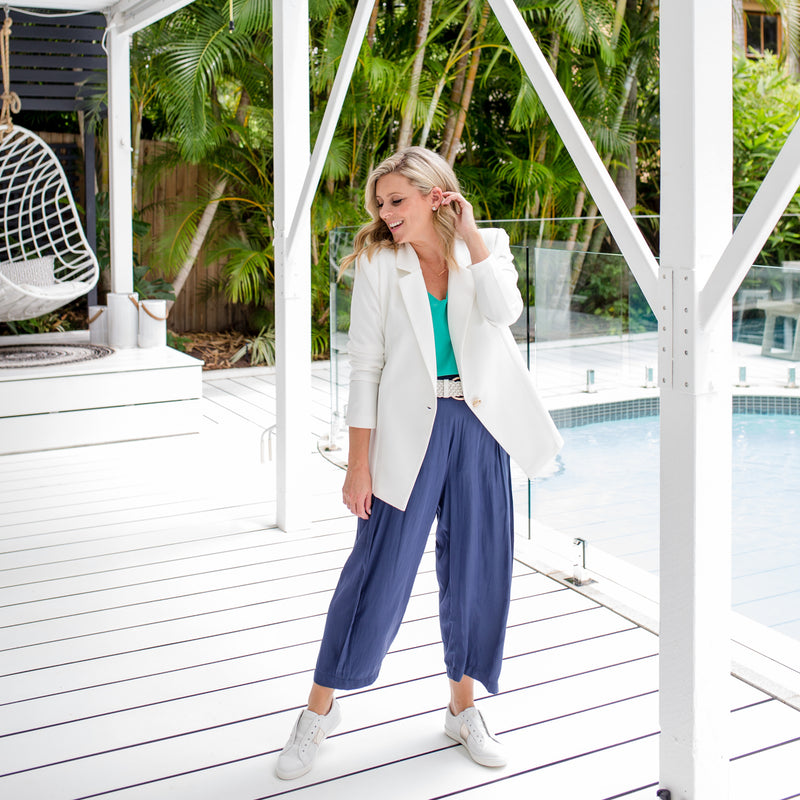 Brooke is wearing our Helen scuba blazer in ivory on top of Rachael technical cami in green tucked into Maddy technical crop pant in steel blue with white belt and white sneakers.